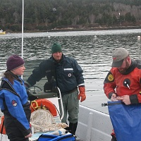 Lee Ann, Mt. Desert Harbor Master Shawn Murphy and Chris check collection bag before dive.